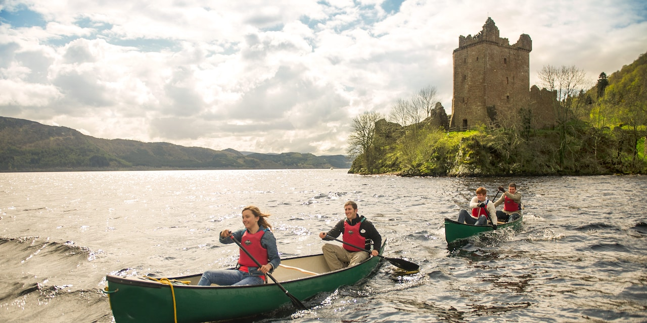 People on 2 rowboats paddling away from a castle on a blustery day