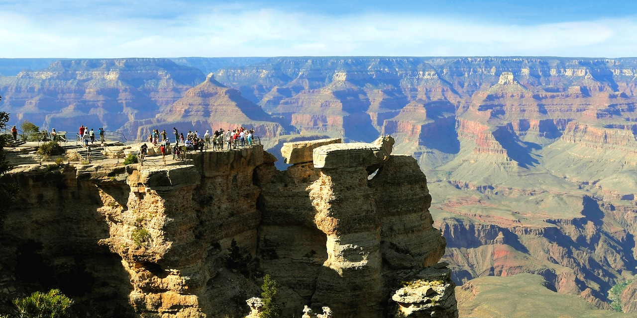 People stand atop a tall mesa viewing the Grand Canyon