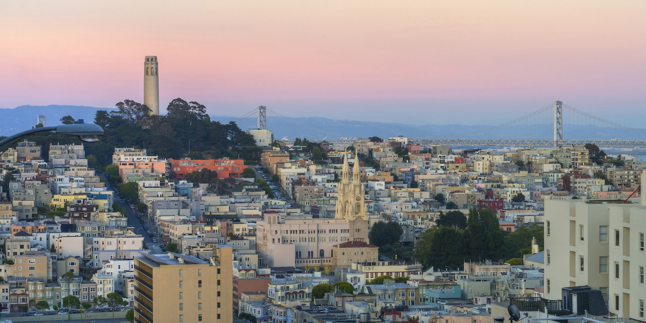 San Francisco at dusk, featuring the Coit Tower and Bay Bridge