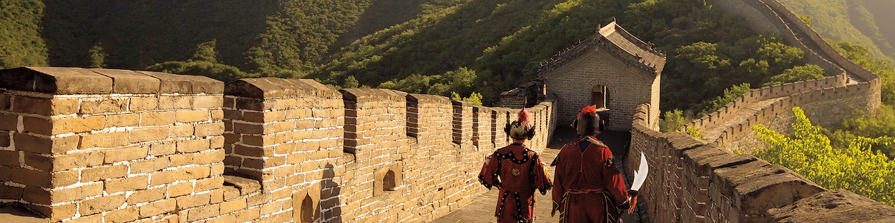 2 men in traditional Chinese clothes walk along the Great Wall of China
