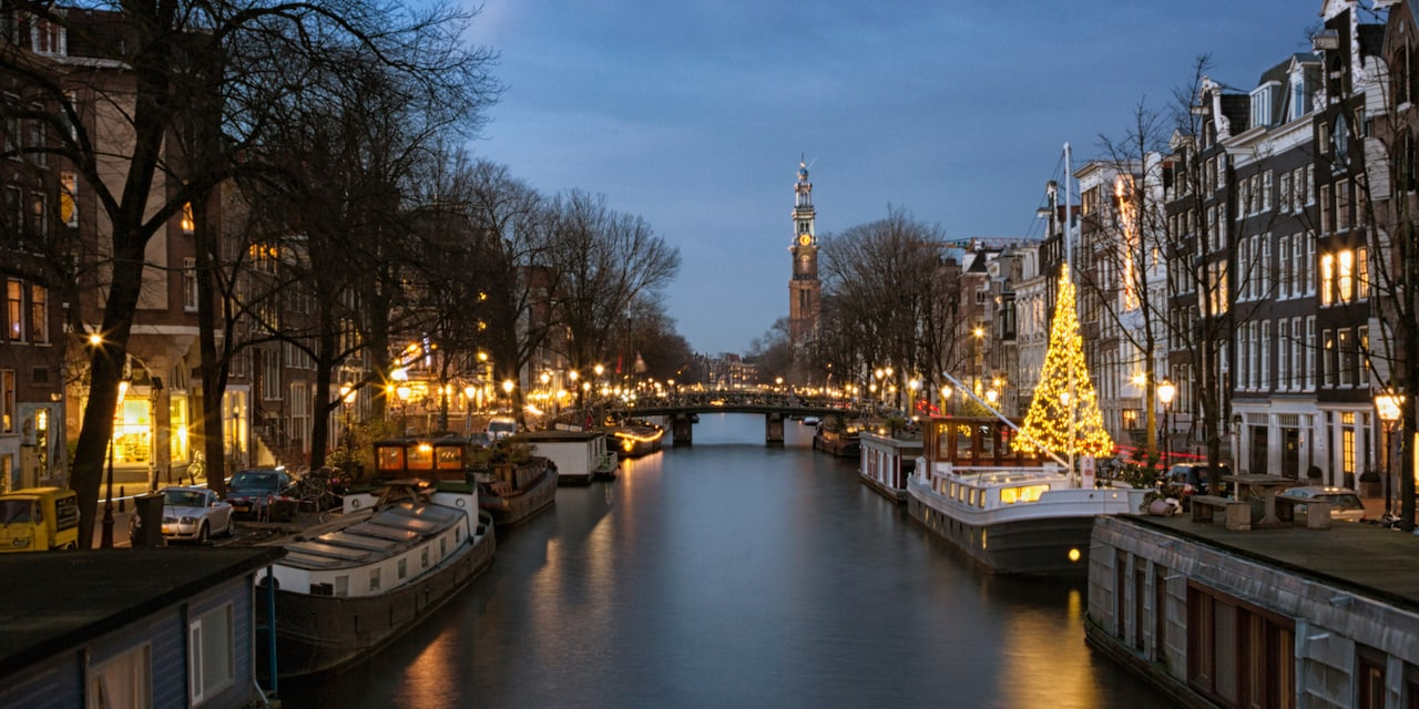 At twilight, boats docked near a bridge and a Christmas tree on a canal flanked with lit buildings