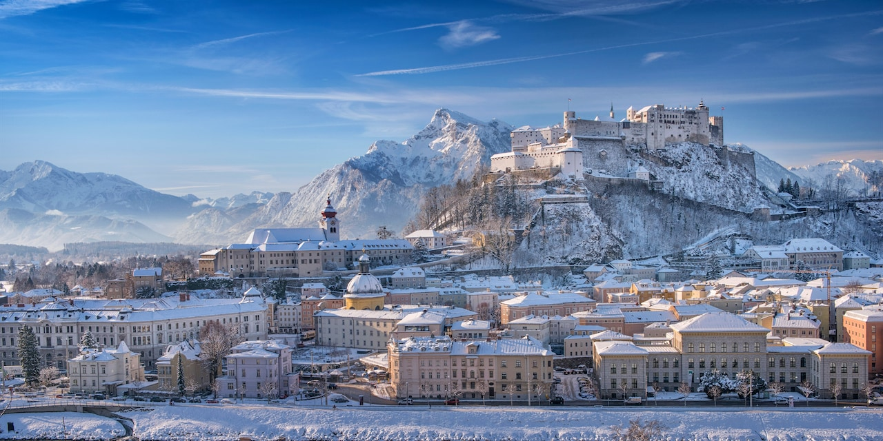 Historic Salzburg with snow covering the streets, buildings and surrounding mountains