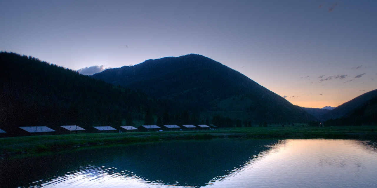 Cabins by a river at daybreak