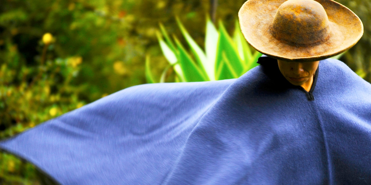 A man wearing a traditional Ecuadorian cape and brimmed hat walks through the jungle