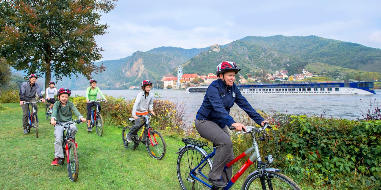 An Adventure guide leads a family biking along the shore of the Danube River