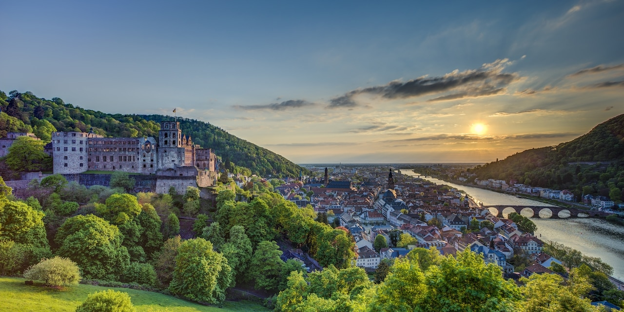 A castle looms over a charming town on a river
