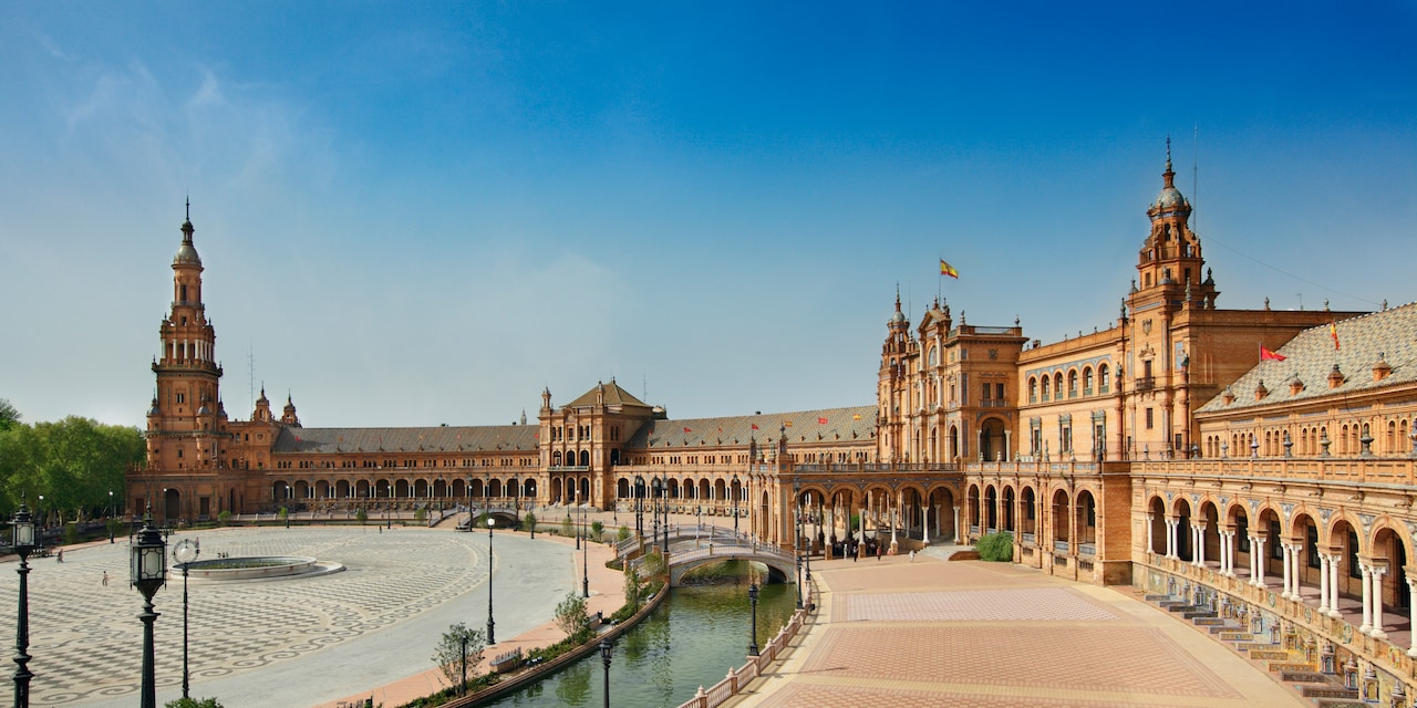 A canal winds around Seville's Plaza de España with its circular tiled patio and stately buildings