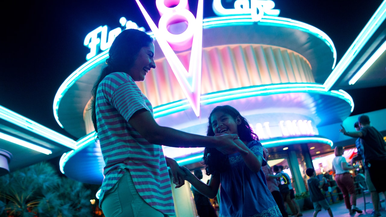 A woman and daughter dance under the neon glow of Flo's V8 Café