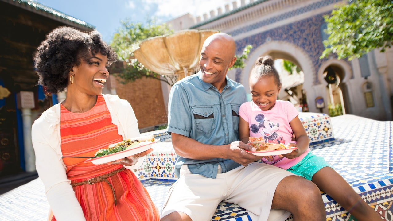 A mom, dad and daughter laughing while enjoying food by a fountain in the Morocco Pavilion at Epcot
