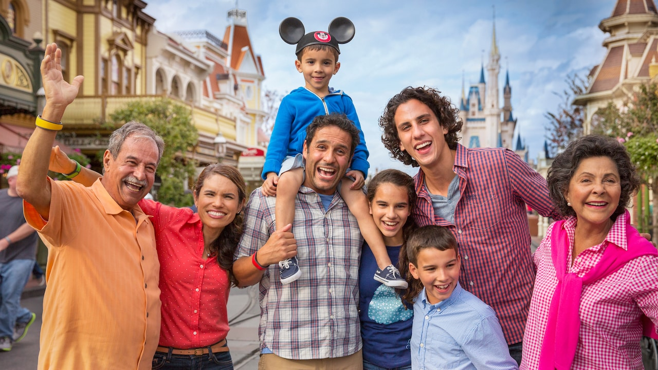 A large family poses together with the Cinderella Castle in the background
