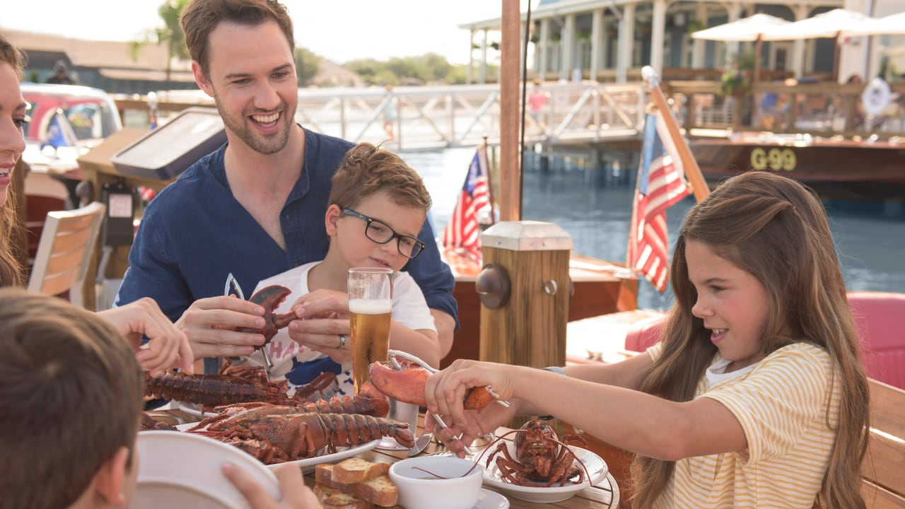 A young girl cracks a lobster claw, as her brother and father sit with her at a dockside table containing a beer and a plate of lobster