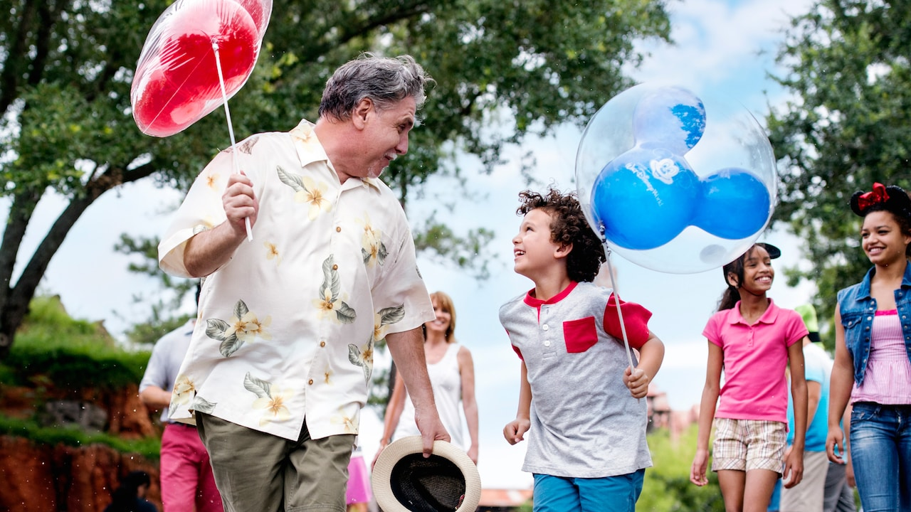 With other Walt Disney World Guests behind them, a grandfather and grandson share a smile as they walk together holding Mickey Mouse balloons.