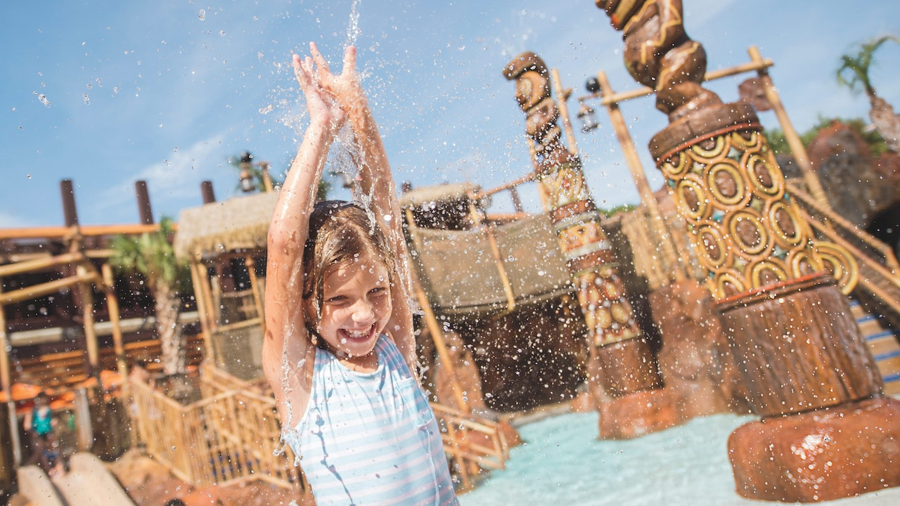 A young female Guest splashing about around a water play area at Disney's Polynesian Village Resort