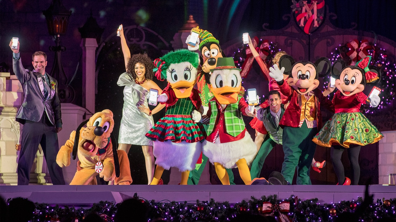 A stage performance featuring performers in holiday attire alongside Mickey and Minnie Mouse, Donald and Daisy Duck, Goofy and Pluto