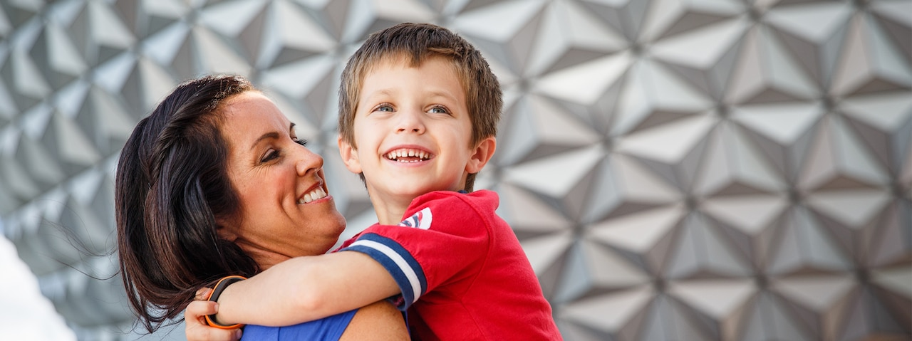 A smiling mother holds her young son in his arms in front of Spaceship Earth at EPCOT