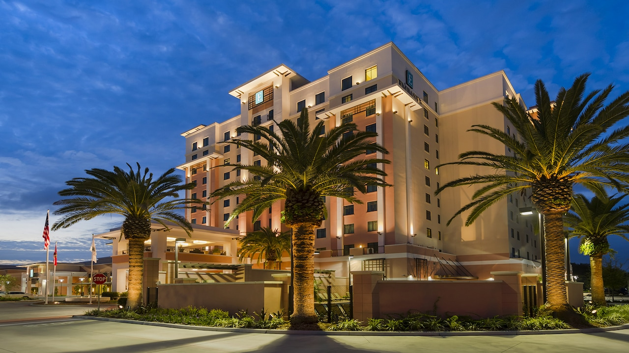 The exterior of Embassy Suites Orlando — Lake Buena Vista South with palm trees and sophisticated architecture.
