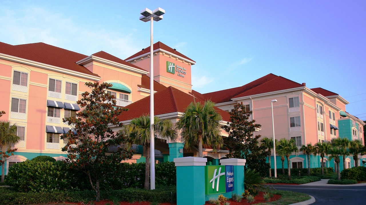 The exterior of the Holiday Inn Express, with palm trees and lush landscaping.