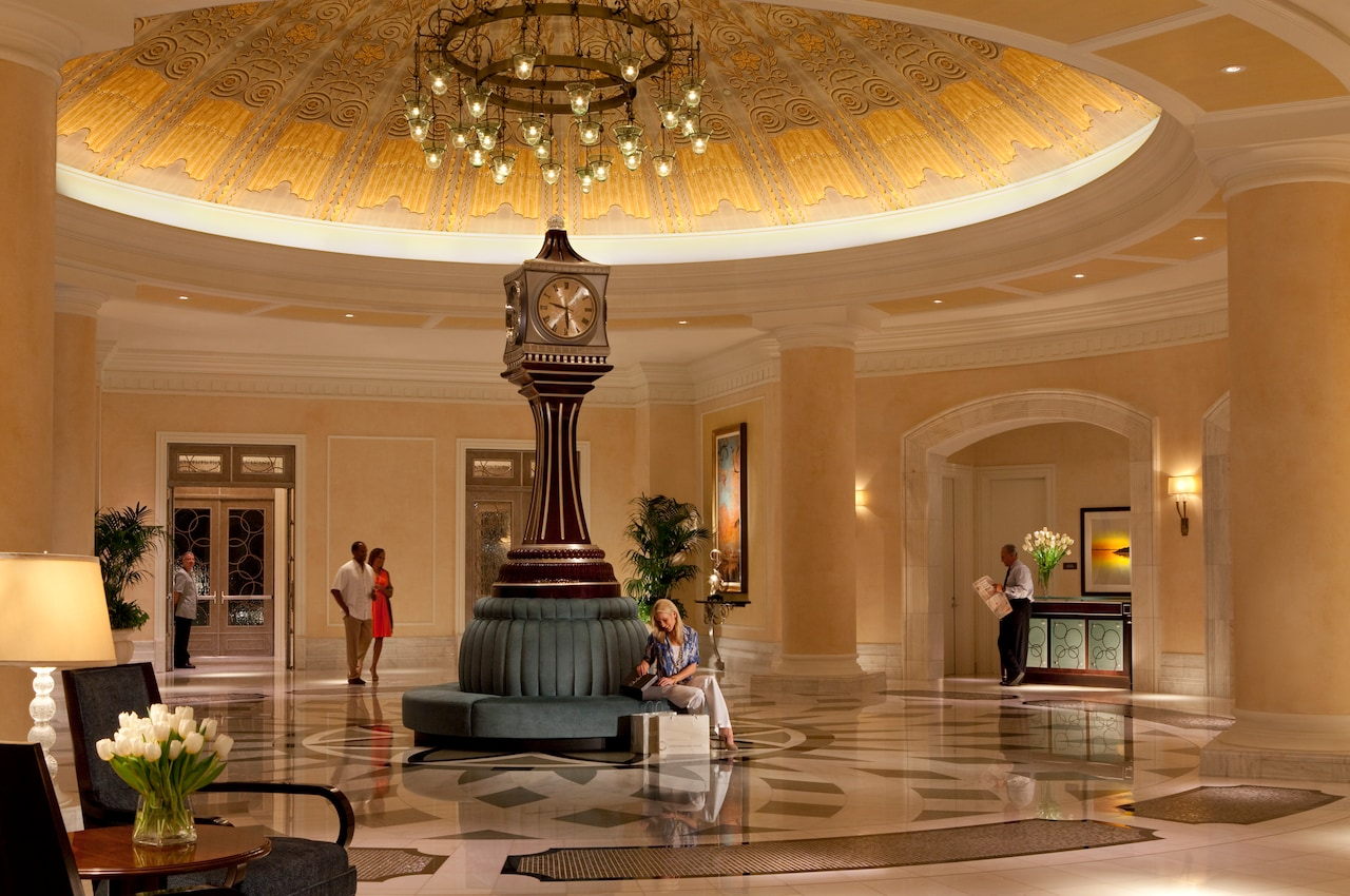 The hotel lobby, with a marble patterned floor, a rotunda marked with columns and a rounded banquet in the center supporting a tall clock beneath a domed ceiling