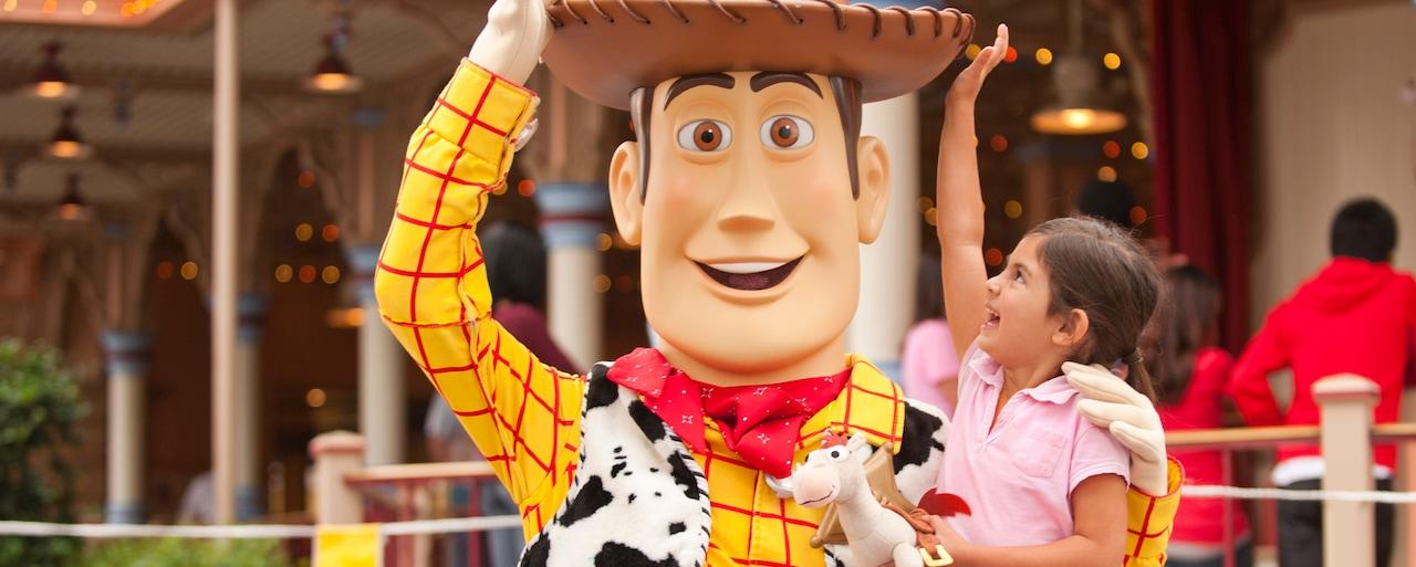 El personaje Woody interactúa con una niña que le toca su sombrero de vaquero y trae un caballo de juguete Bullseye