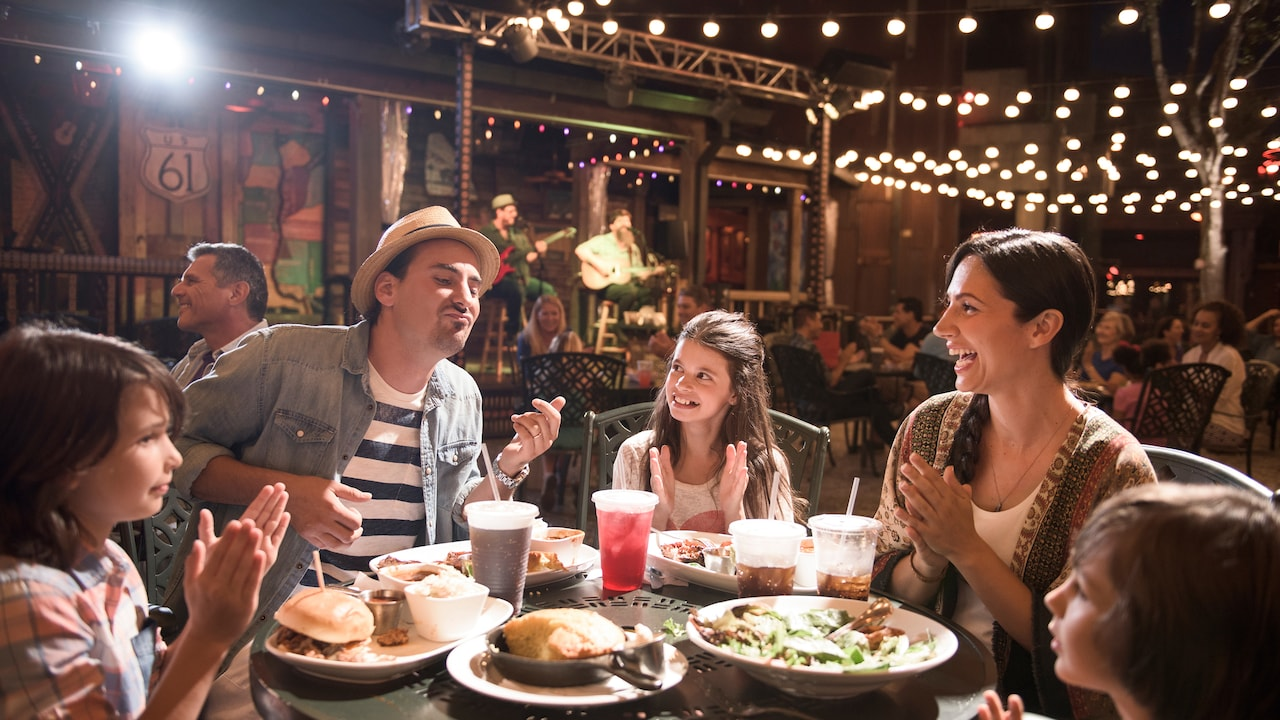A family enjoys dinner at a Disney Springs restaurant while a live band plays music in the background