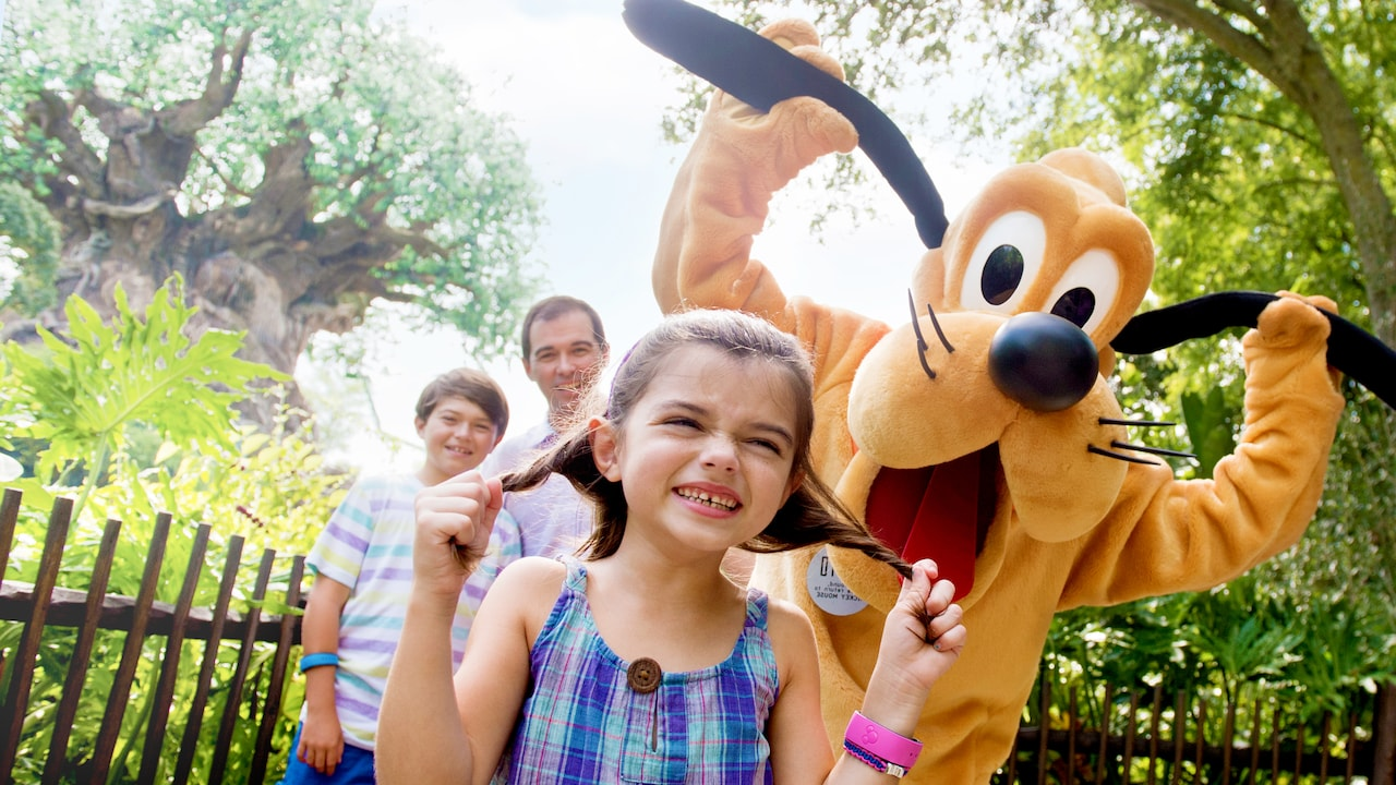 A young female Guest laughs while holding her hair as if it were dog ears while Pluto does the same