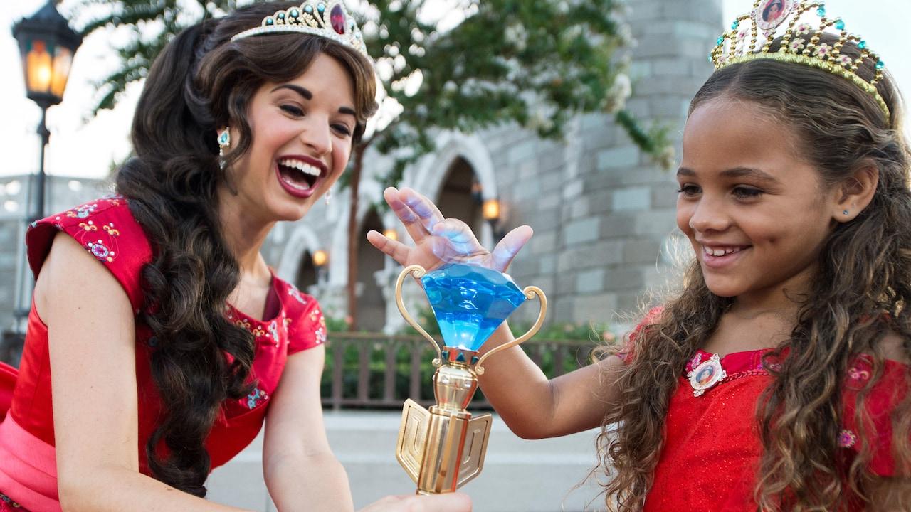A Princesa Elena sorri enquanto uma menina vestida com uma fantasia da Princesa Elena toca o cetro de cristal dela