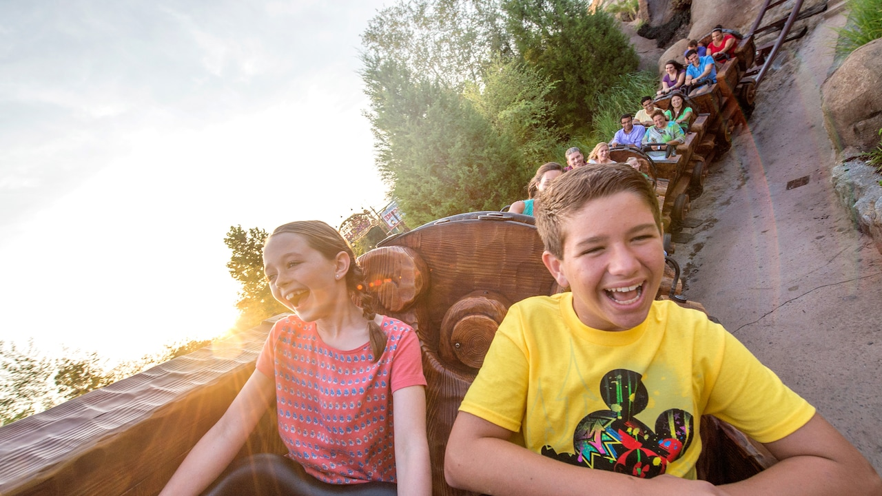 A brother and sister smile as they ride the Seven Dwarfs Mine Train