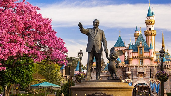 The Partners statue featuring Walt Disney and Mickey Mouse stands in front of Sleeping Beauty Castle at Disneyland Park in California