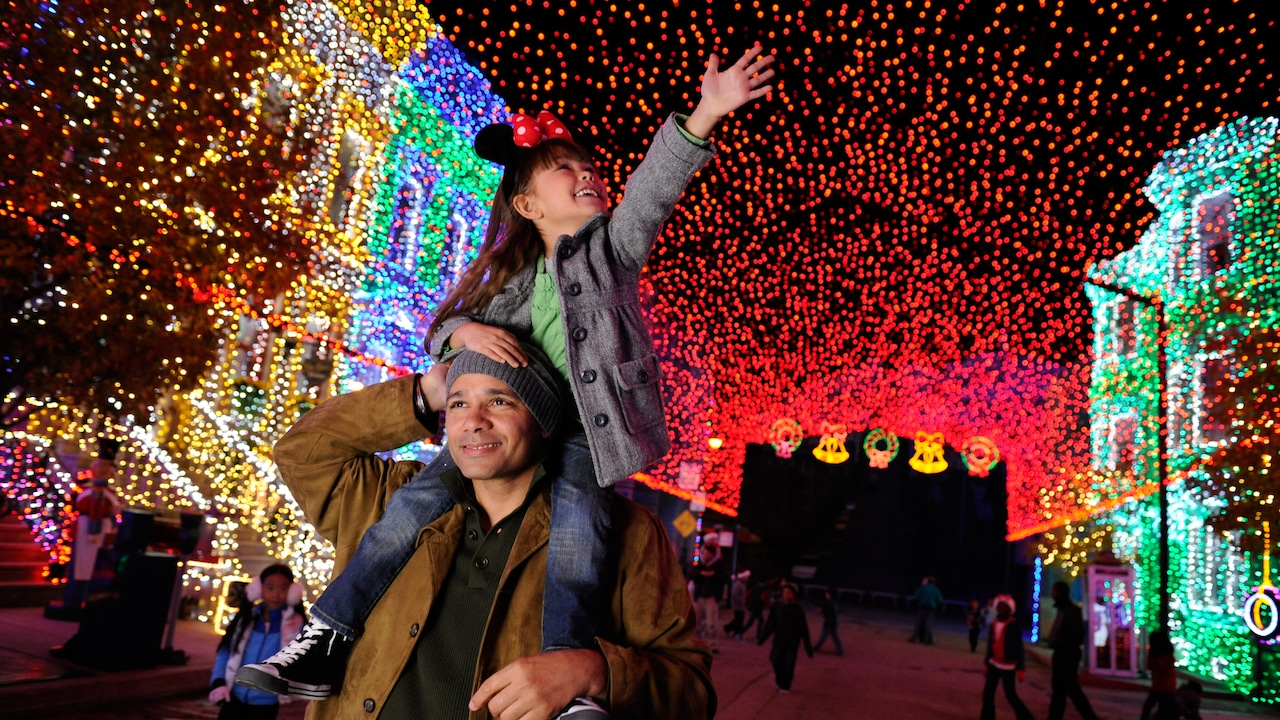 A young girl with a Minnie Mouse ear hat sits on her father's shoulders and reaches up towards a canopy of holiday lights strung across a city street
