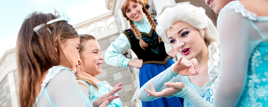 Queen Elsa entertains a smiling group of young princesses while her sister princess Anna looks on
