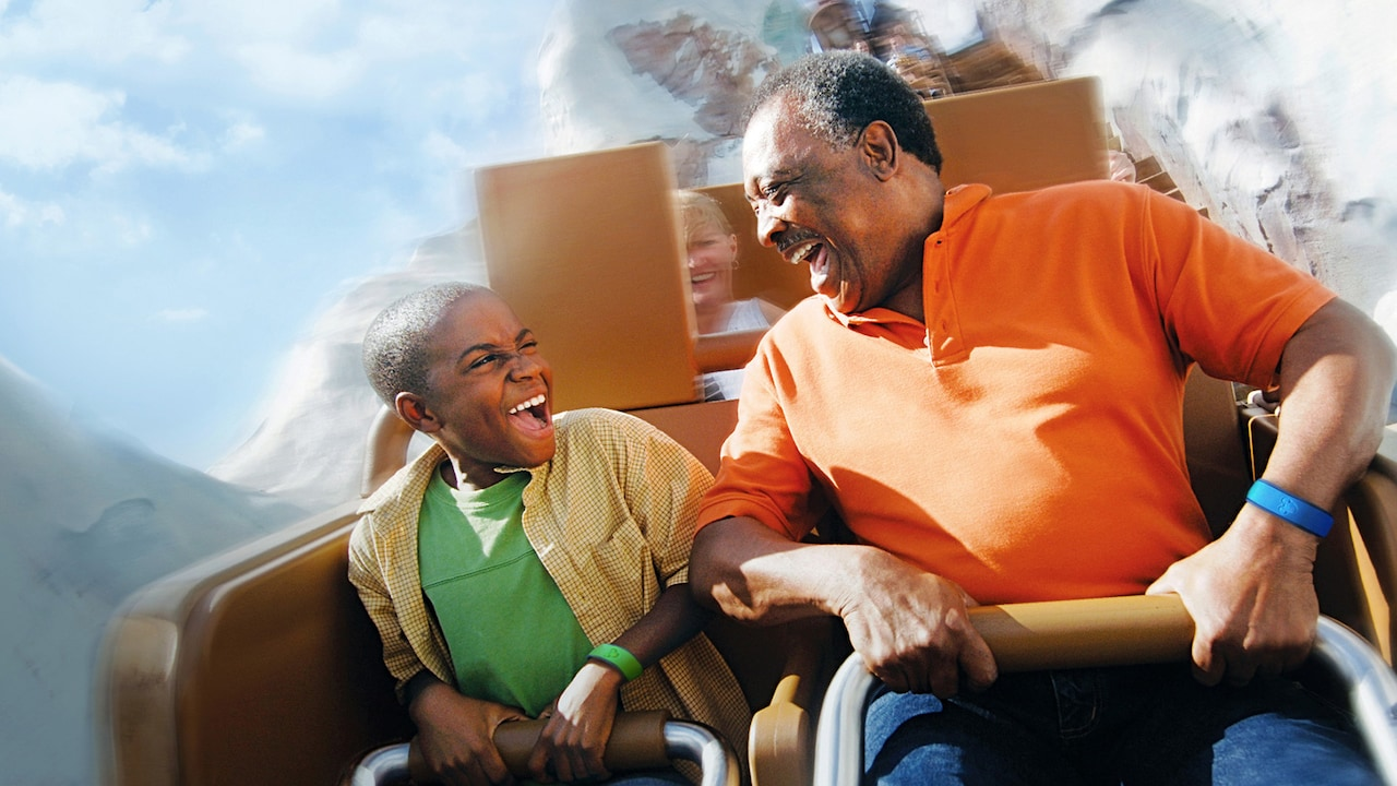A father and son smile at each other as they ride Expedition Everest