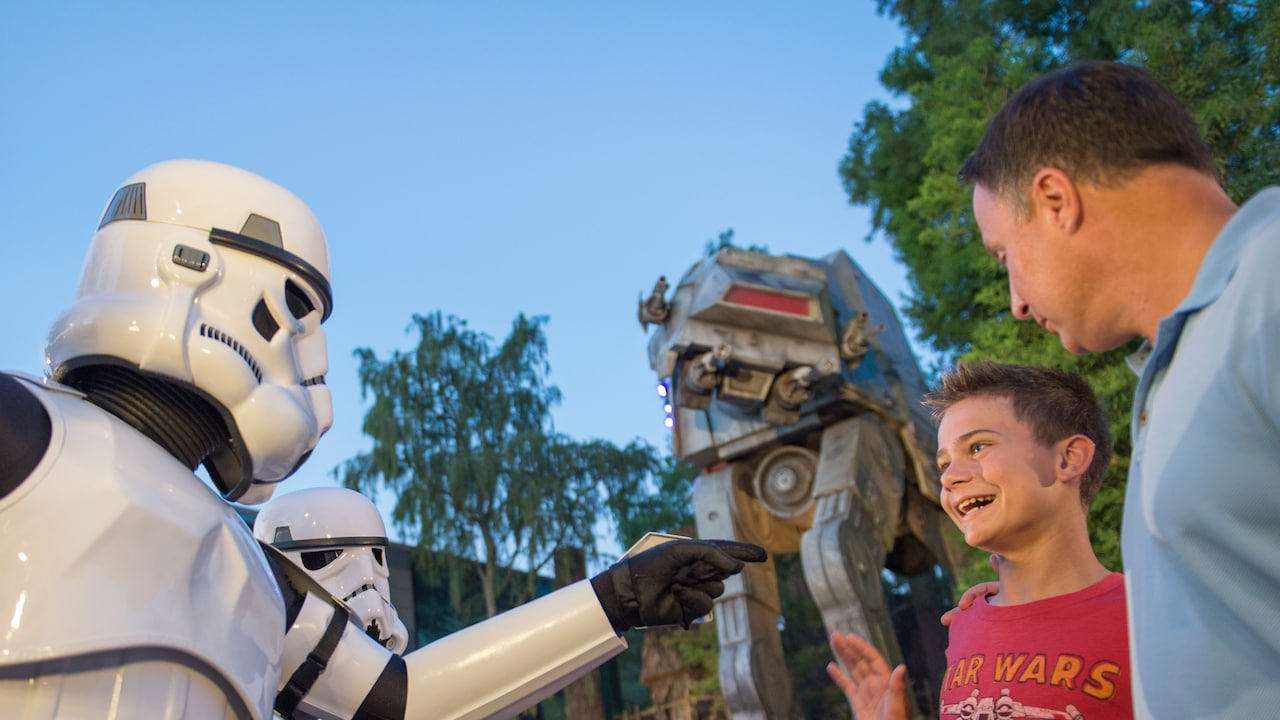 A boy and his father play along with some Star Wars Stormtroopers