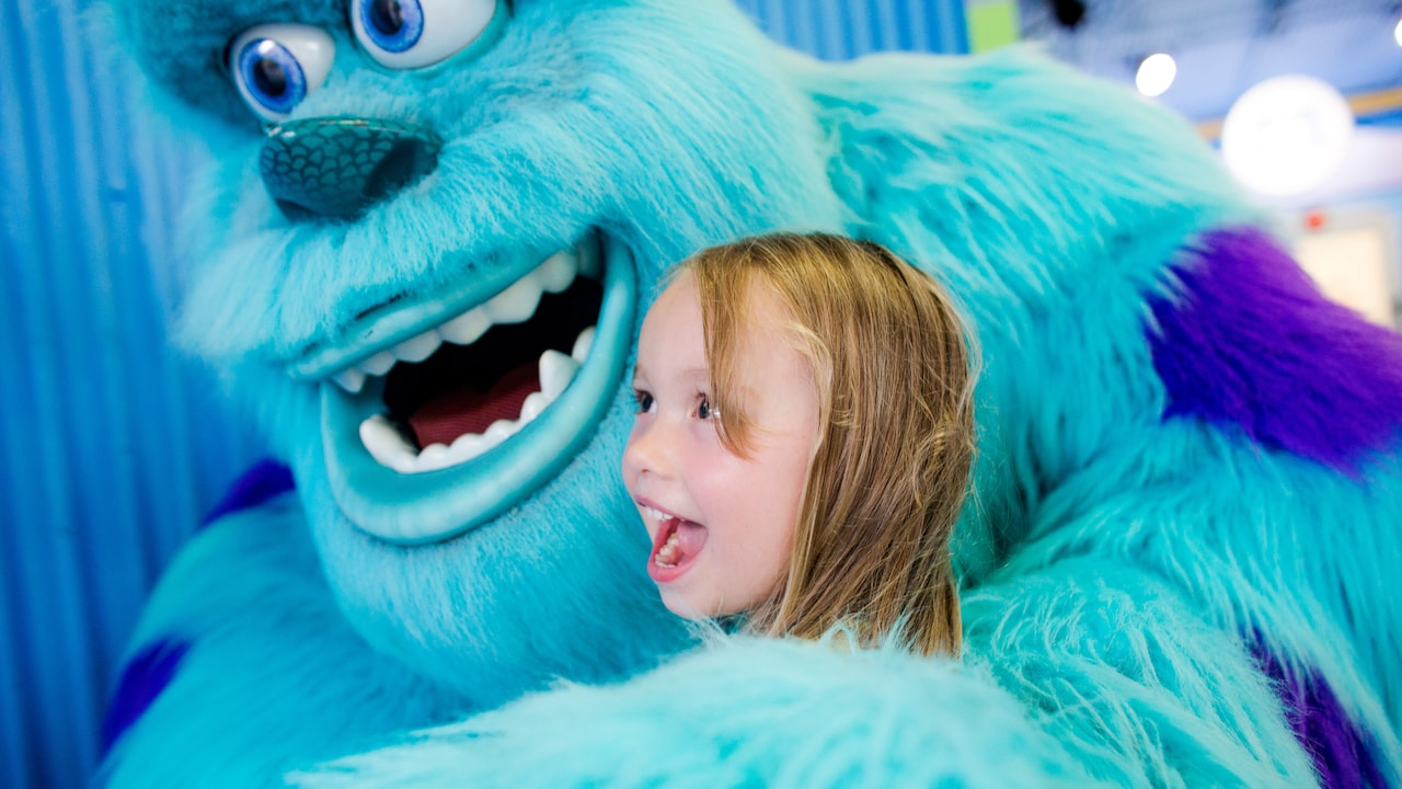 The large furry monster Sulley embraces a smiling little girl