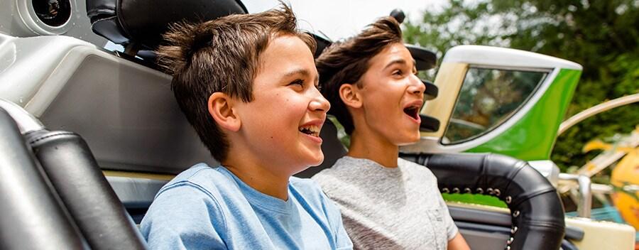 Dos Huéspedes jóvenes disfrutan de un paseo emocionante en una atracción, en Walt Disney World Resort