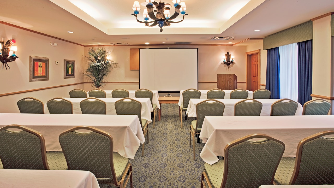 A meeting room with several tables with chairs facing a lectern next to a projection screen
