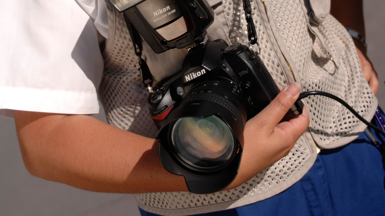 A PhotoPass photographer holds a professional digital camera with a flash and a neck strap