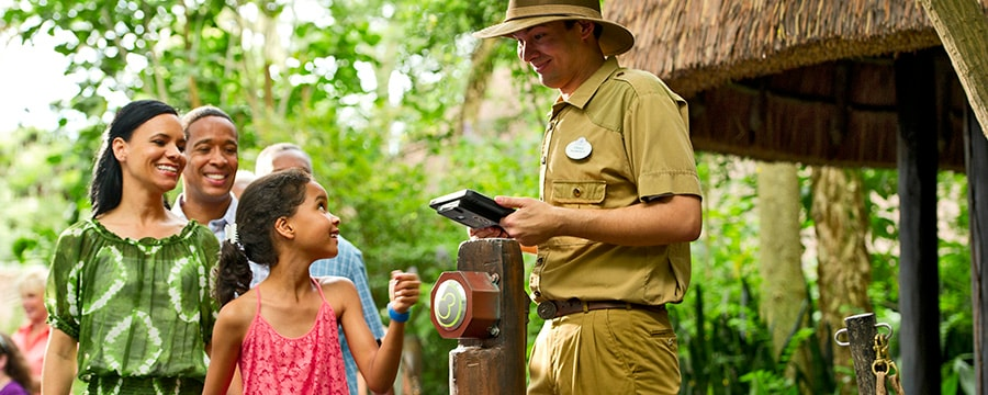 Disney Guests scan their Magic Bands at a touch point as a cast member looks on