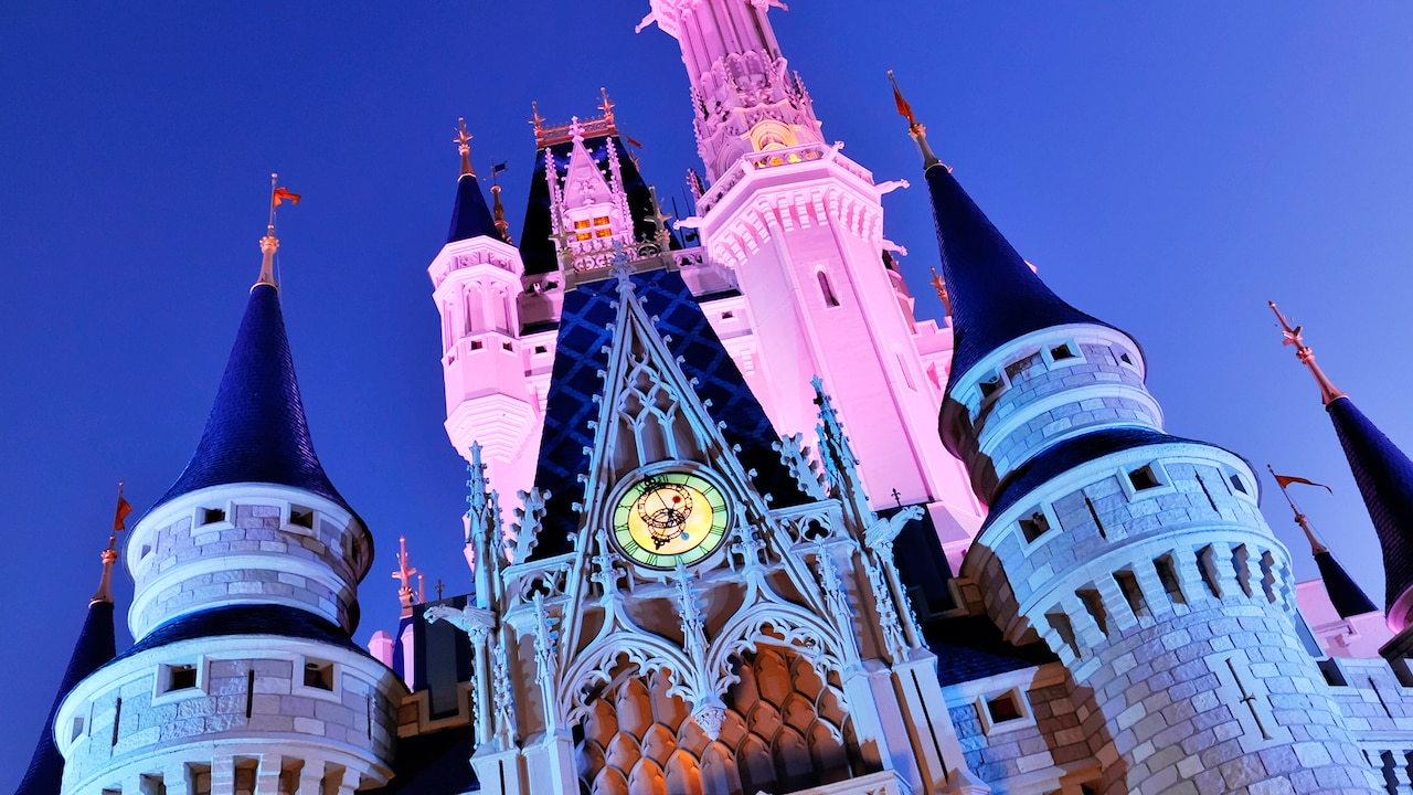 The towers and turrets of Cinderella castle, lit from all sides, stretch into the sky above Fantasyland