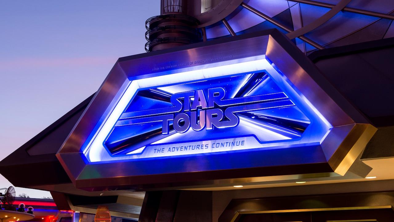 Un letrero iluminado de noche señala la atracción Star Tours The Adventures Continue