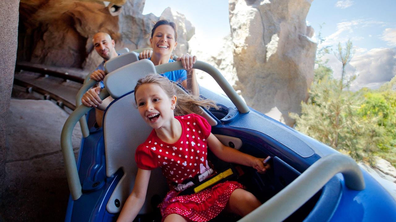 Una niña y sus padres gozan la atracción Matterhorn Bobsleds en uno de los trineos para 3 personas