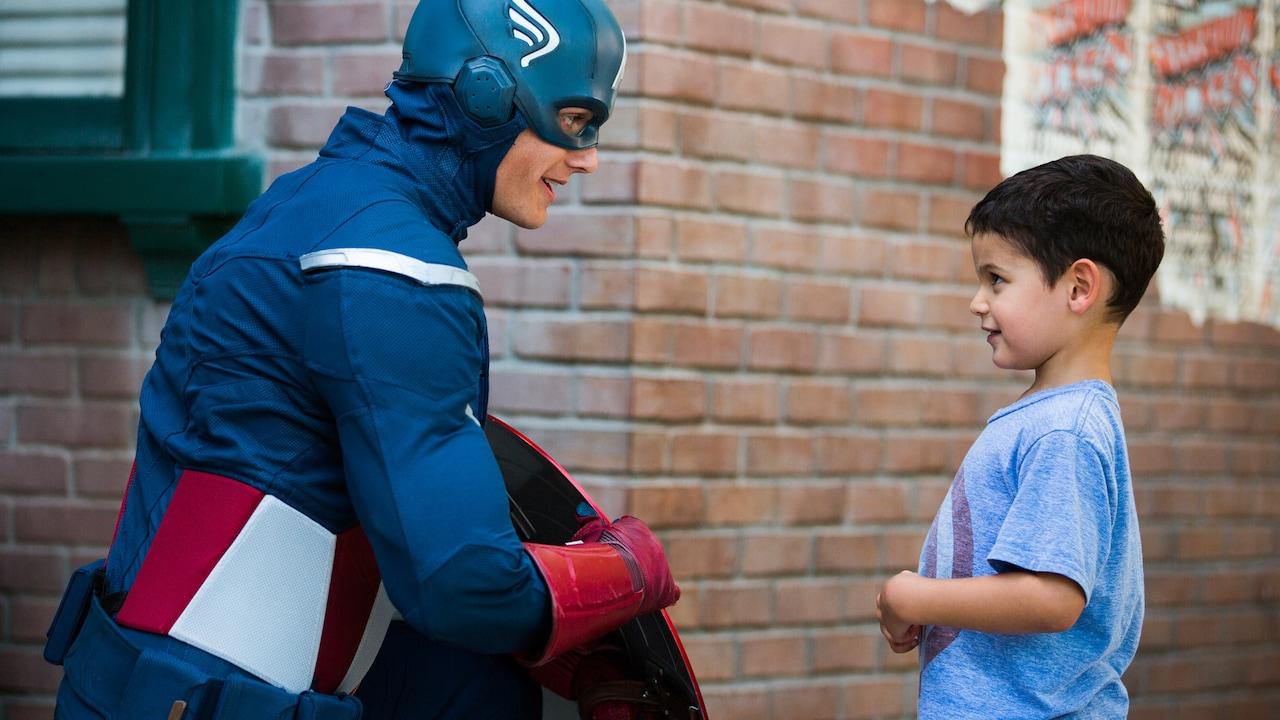 El Capitán América, con su escudo a un lado, se hinca para saludar a un niño