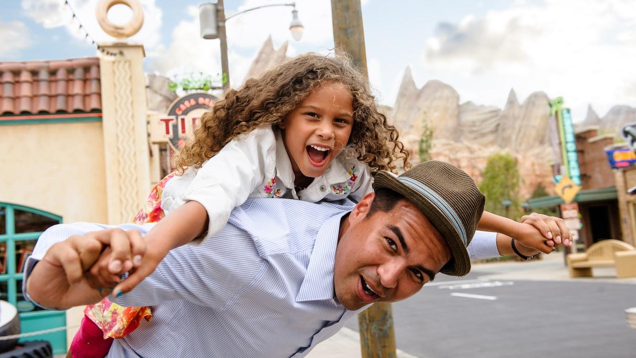 En Cars Land, un papa con sobrero lleva a caballito a su hija de cabellos rizados