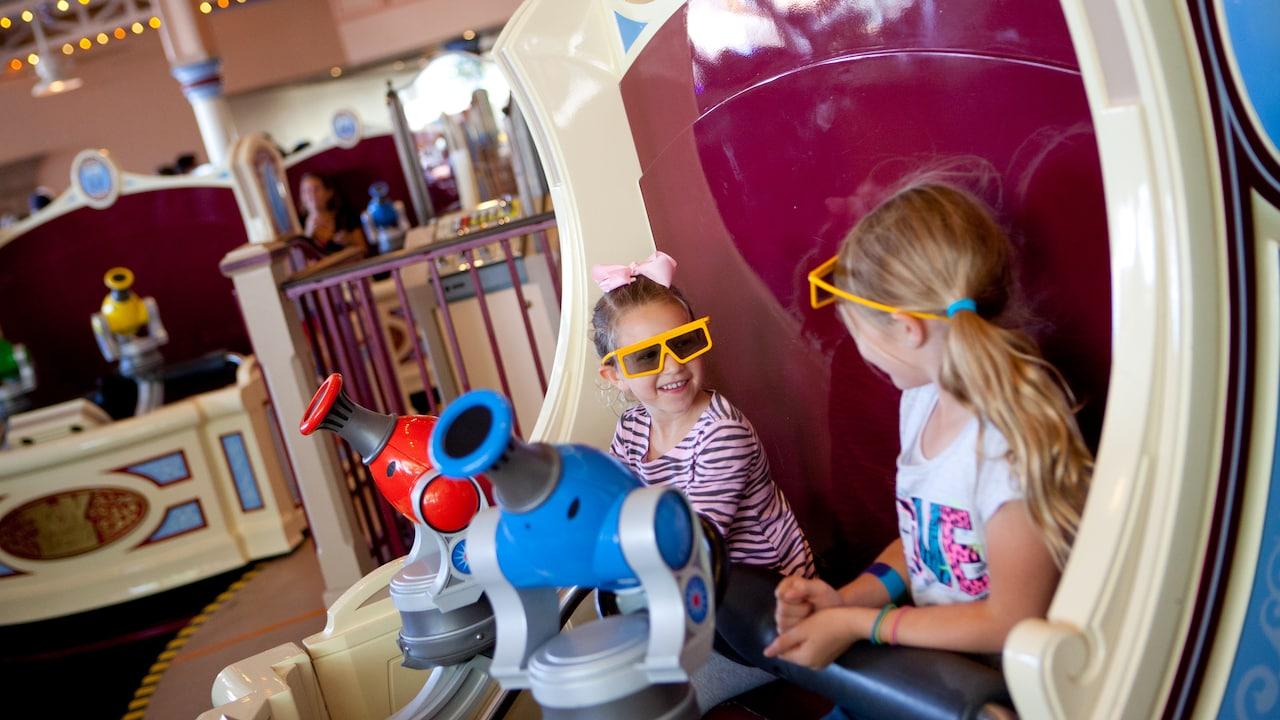 Dos niñas pequeñas van sonrientes en un carro de la atracción Toy Story Midway Mania! con sus lentes de 3D