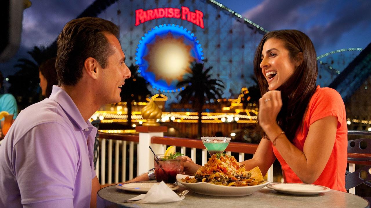 Una pareja disfruta sus bebidas en Cove Bar cerca de California Screamin' en Paradise Pier