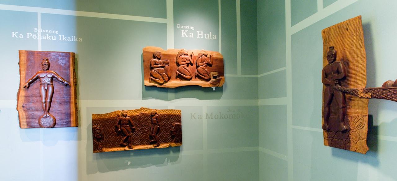 先住民のさまざまな動作を表現した木のレリーフ、その説明を簡潔に示すハワイ語のフレーズと英語の翻訳