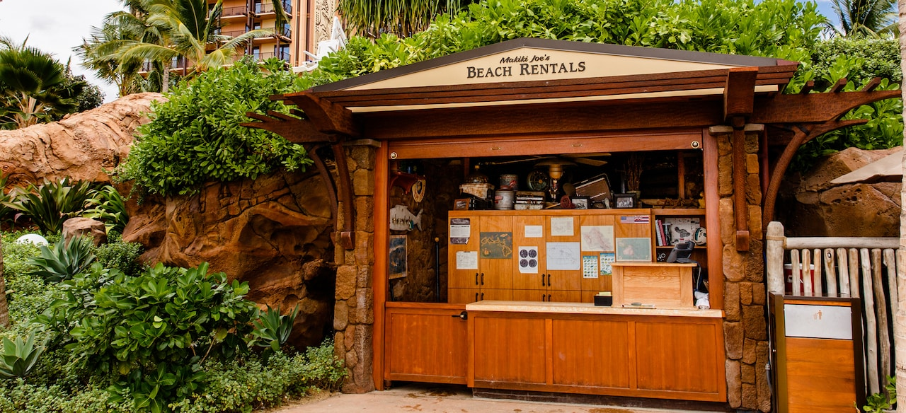 The exterior of Makiki Joe's Beach Rentals, a wooden shack nestled in trees and shrubbery