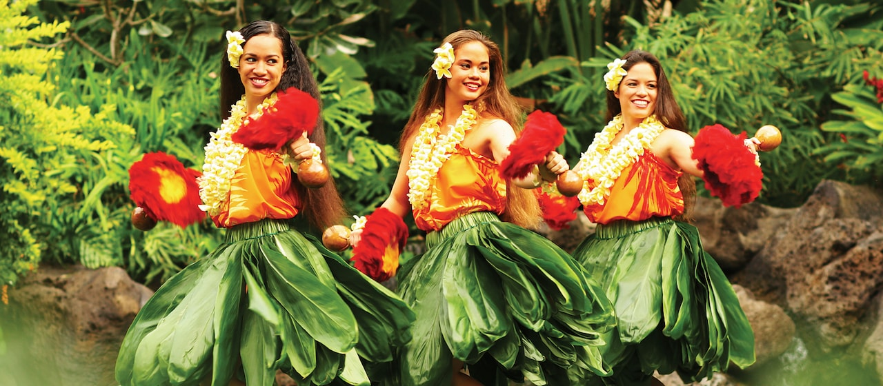 Three festively dressed female hula dancers perform against a lush tropical backdrop at the Alii Luau at Aulani Resort.