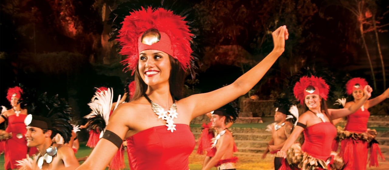 A smiling female dancer in a feathered headdress joins with other festively dressed dancers during a performance in a garden setting.