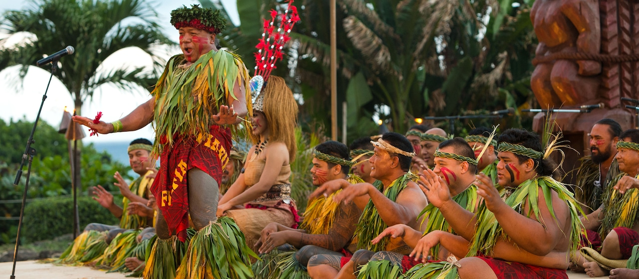 Dancers outfitted in festive Hawaiian dress and adornments entertain at a nighttime performance