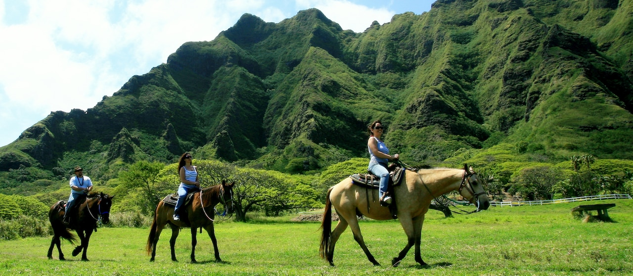 Two women riding horses through a lush Hawaiian valley
